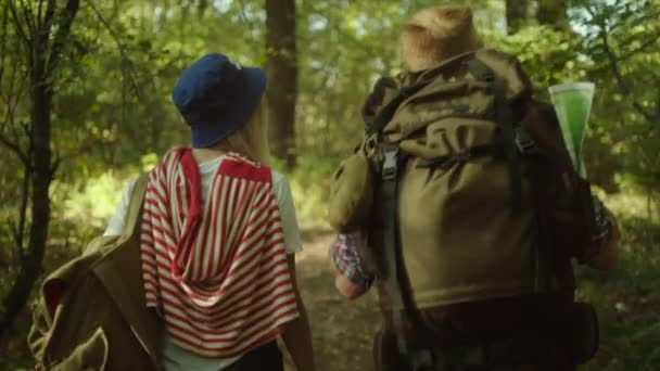 Young couple with backpacks having a walk in the forest