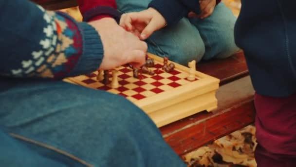 Kleine Jungs spielen Schach mit Opa auf der Bank im Herbstpark