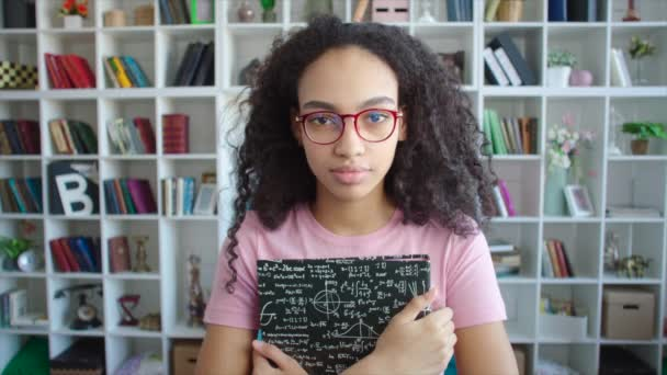 Serious african american female student portrait with textbooks in her hands in university library