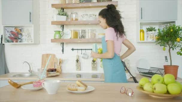 Mladá žena dává květiny do vázy v kuchyni
