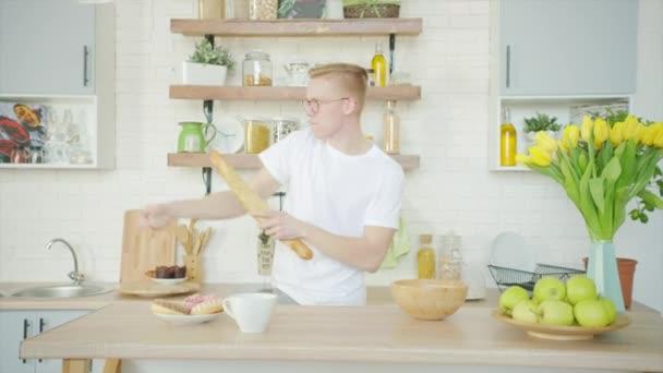 Mladý muž tančí s chlebem, zatímco ráno připravuje snídani v kuchyni