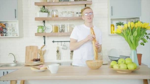 Mladý muž se poflakuje a zpívá s chlebem místo mikrofonu v kuchyni
