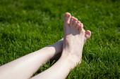 Női lábak zöld füvön