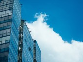 Clouds float past the windows of your apartment in a skyscraper.