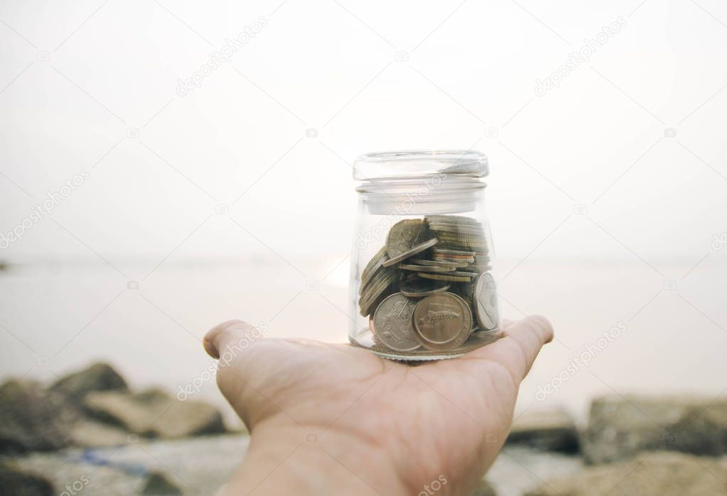 selective focus and blurred image concept.cropped hand holding transparent glass jar with coin.blur background at the beach with sunlight during sunset