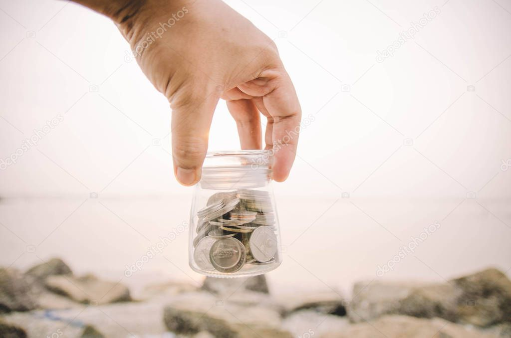hand holding top of glass jar contain with coin concept.blur background at the beach during sunset