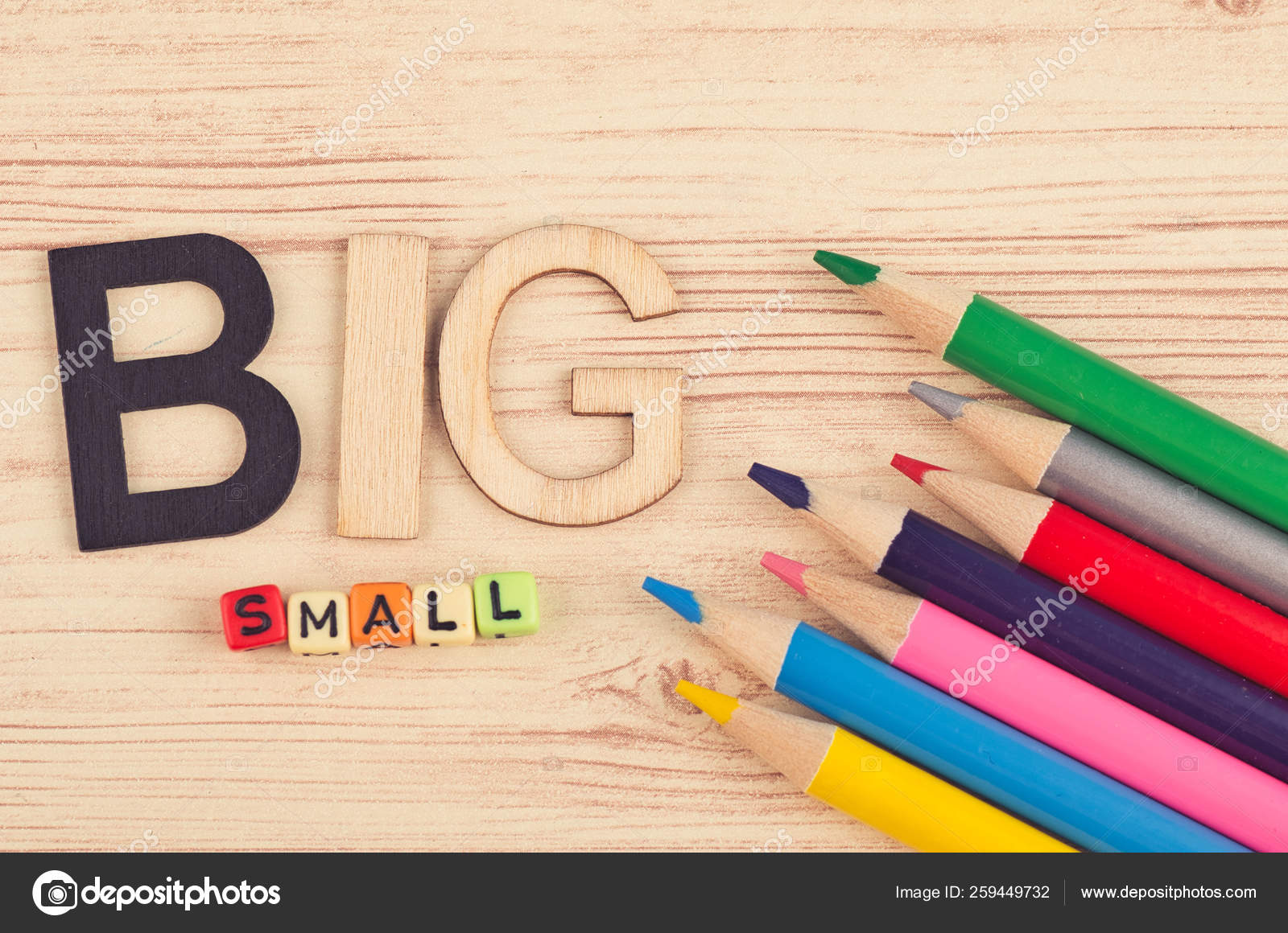 Business Concept Colorful Pencils And Word Big Small On Wooden