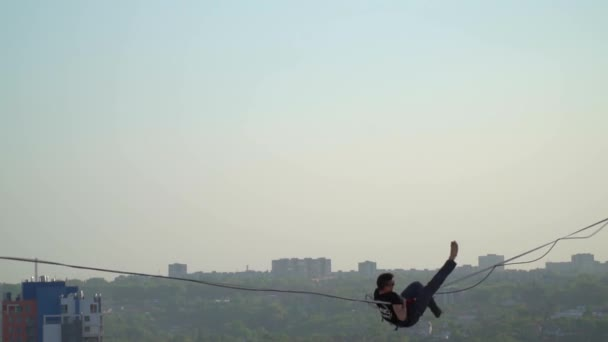 A man in sunglasses walks along a tight rope and falls down, slow motion