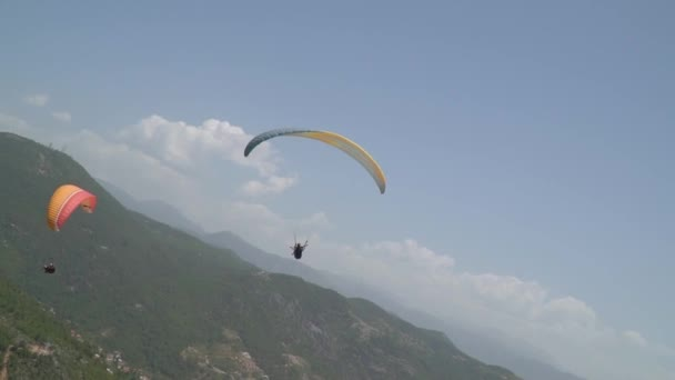Travelers fly by parachute near the mountains