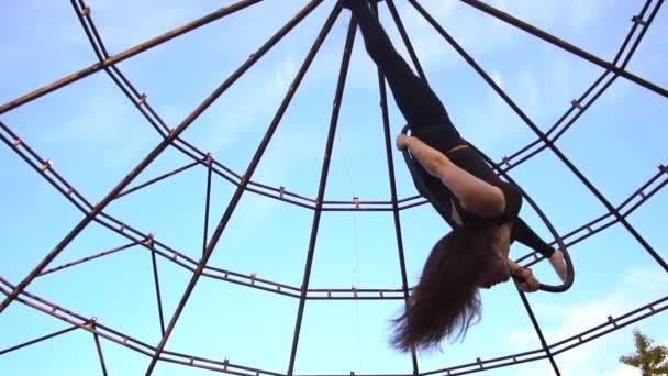 Zpomalené střílení dívka viset hlavou dolů v kruhu pro vzdušné akrobacie a dělá vlákna