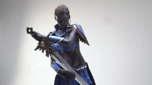 Seriózní žena v černé a bílé tělo umění pózuje s mečem