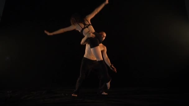 The pair shows acrobatics tricks, the woman sits on the floor of the man and arches