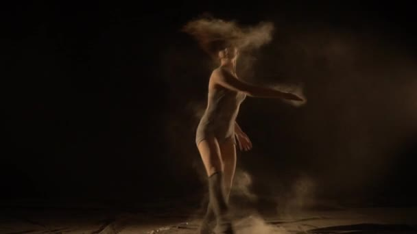 Beautiful girl with long hair dancing in the sand, slow motion