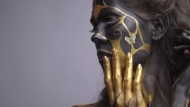 Portrait shot, model in black and gold body art corrects hair and looks at the camera, slow motion