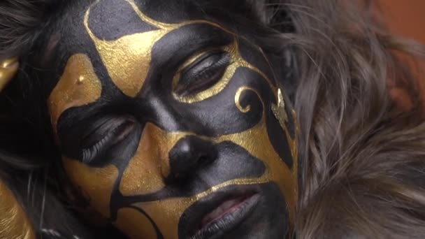 Model with long eyelashes in a black gold make-up posing on a brown background, close up