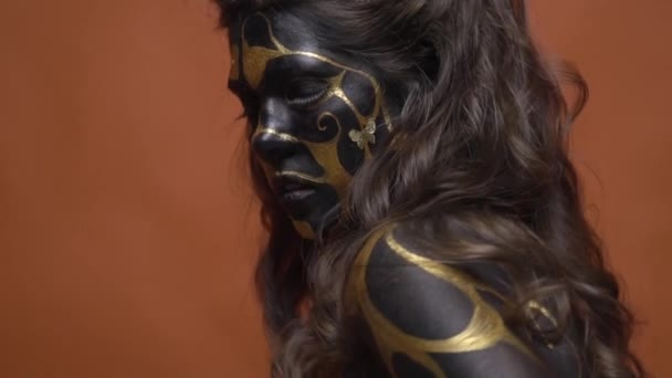 A girl in a black makeup with golden patterns turns on the camera, slow motion