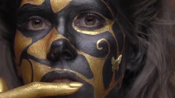 Sensual model in black gold body art touches her lip