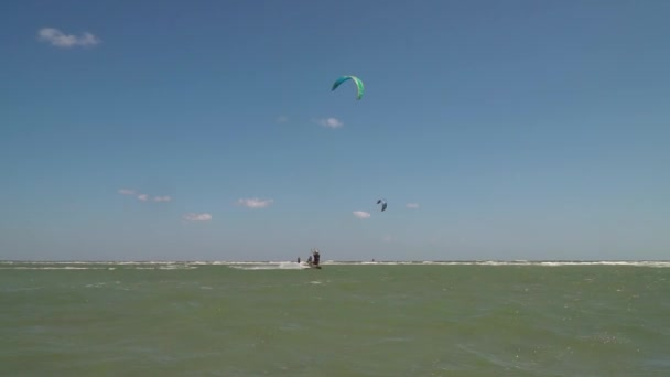 A man on a kitesurf jumps high in the air against the backdrop of a beach camp