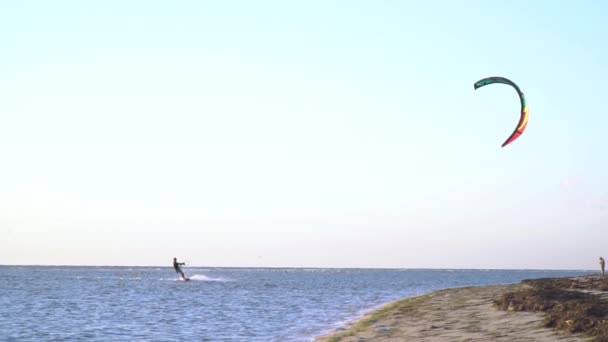 Slow shooting of a man against the cloudless sky is engaged in kitesurfing