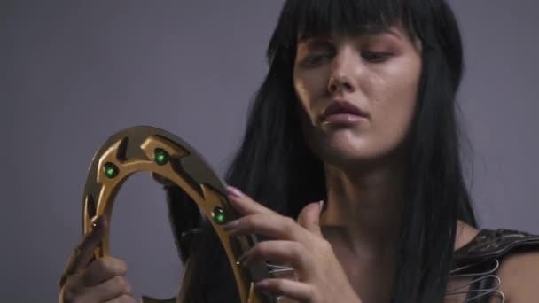 Amazon dívka v brnění kontroluje závažnost bojových disku a čeká na někoho