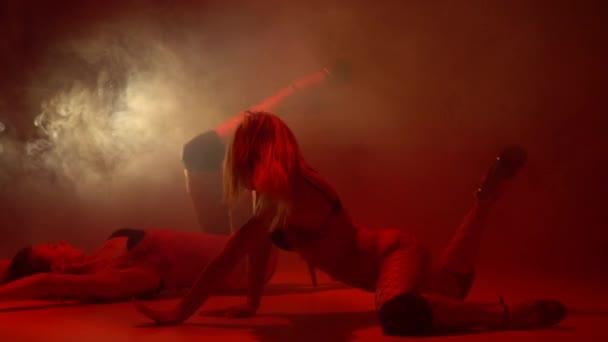 Egy pár női, szexi harisnya a szalag tánc táncolt a füst, lassú mozgás