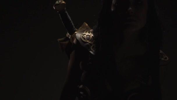 Sexy dívka bojovník v brnění stojí ve tmě a pózy, pomalý pohyb