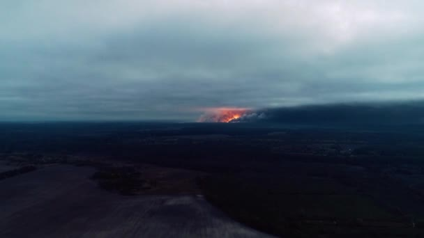 Huge explosion with the flames in the field, aerial shot