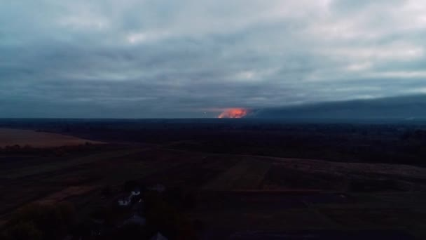 Horizon covered by the multiple explosions and huge amounts of smoke, with the little village appearing in the shot, aerial shot