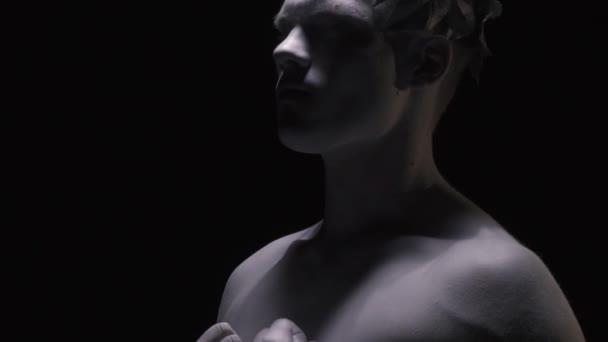 Élő szobor a görög ember becsukja a szemét, és felemeli a fejét