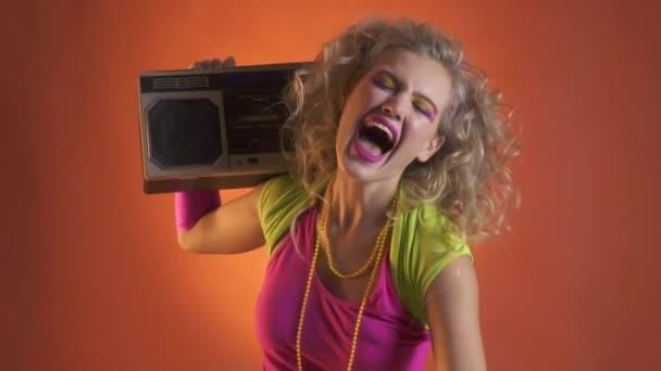 Mladá blond žena baví tanec s boombox, retro styl