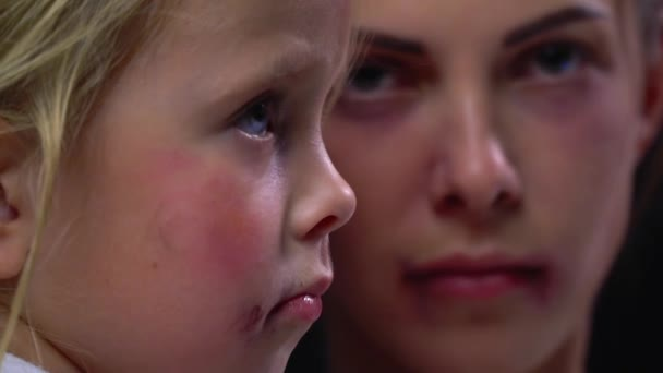 Bruised little girl sitting with her beaten mother, domestic violence, sad family