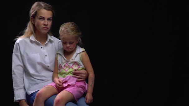 Angry mother with beaten up daughter on her lap, child abuse, social issues