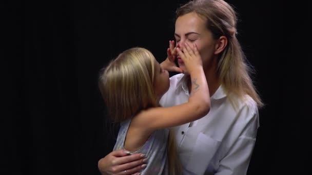 Roztomilý scéna, malá dcerka líbat její matka vsedě na její klín, černé pozadí