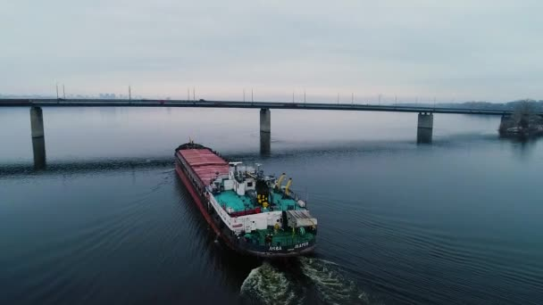 Amazing big cargo ship sailing on the river and going under the bridge