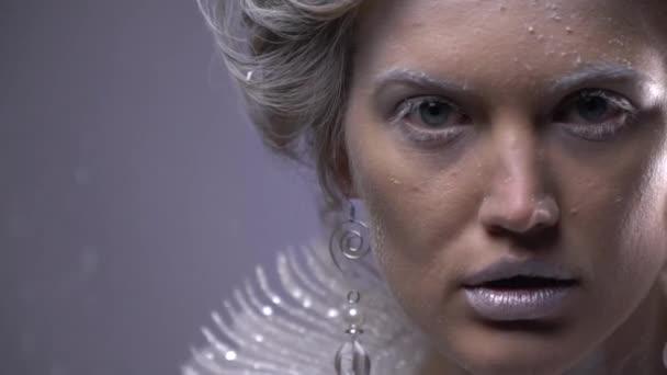 Detailní záběr ženy s bílými vlasy a sněhové vločky na její tváři