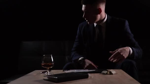Angry and frustrated businessman rolls up his sleeves and making lines of cocaine with a credit card