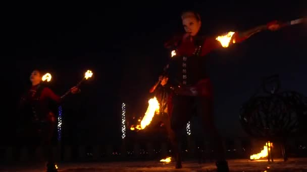 Three people perform a fire show on the street