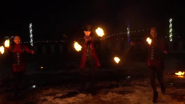 Beautiful fire show by two female and a male performers, on the street, with night city on the background