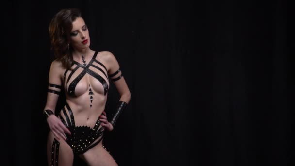 Slow motion shot of a young woman covered in tape with metal spikes, posing in the studio