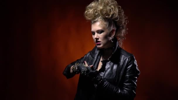 Edgy rocker girl with crazy hairstyle, showing middle finger