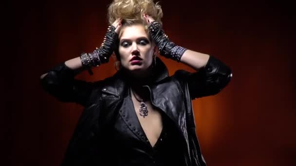 Posing rocker girl in leather jacket and with amazing hairstyle