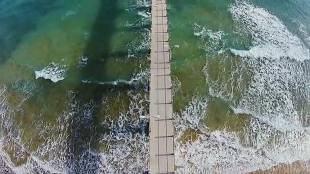 Long pier surrounded by amazing waves, Porto Santo, Portugal, aerial shot
