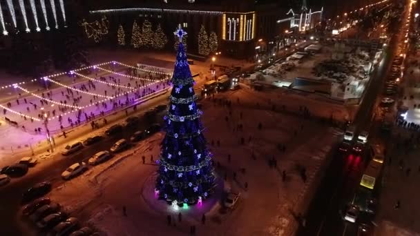 Amazing huge Christmas tree, ice rink and decorated building at night, aerial shot