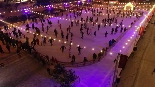 Barevné zimní stadion plný mnoha lidí, bruslení, večerní osvětlení, letecký snímek