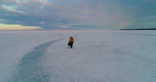 A man walking on the frozen river, beautiful sunset and horizon, 4k