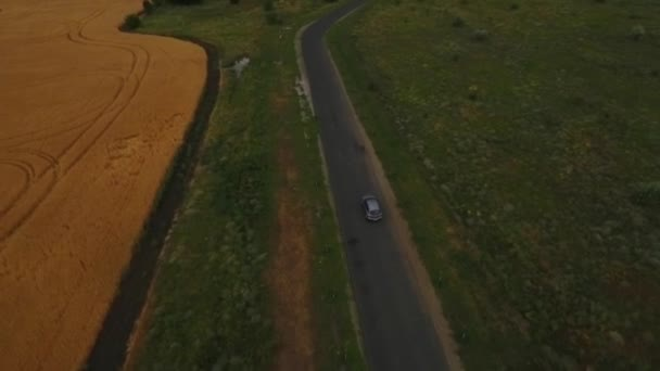 Aerial shot of a countryside road and a car is driving on it, amazing view, before the thunderstorm