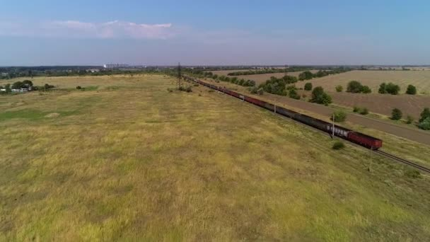 Gorgeous countryside view on the fields and railway with a big cargo train