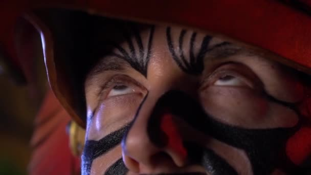 Creepy shaman with black patterns of paint on his face and headdress, rolling his eyes