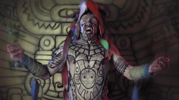 Creepy aztec warrior getting ready before the battle, screaming and shaking with his arms spread