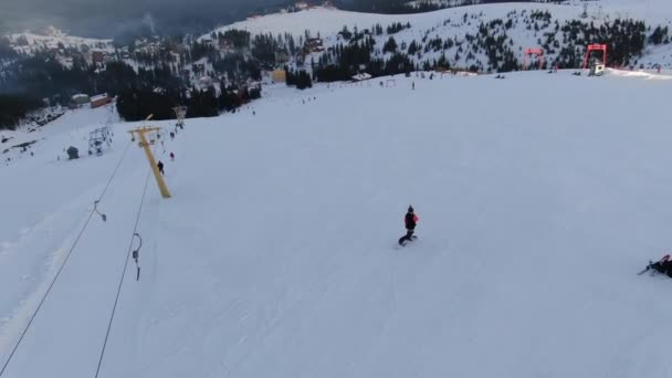 Beautiful snowy slope in the ski resort, lots of people are skiing and snowboarding, aerial shot